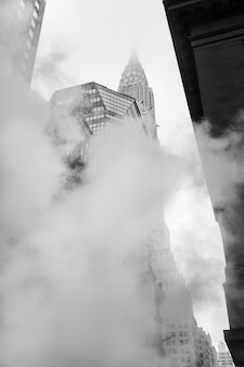 New york, verenigde staten - 3 mei 2016: empire state building. manhattan straatbeeld. wolk van damp uit de metro in de straten van manhattan in nyc. typisch uitzicht op manhattan