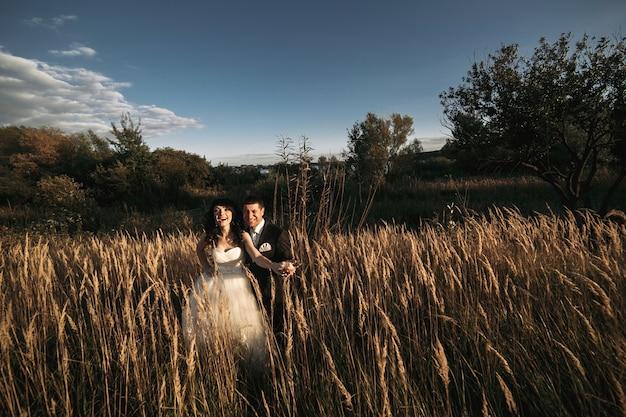 Newlyweds lachen in het veld