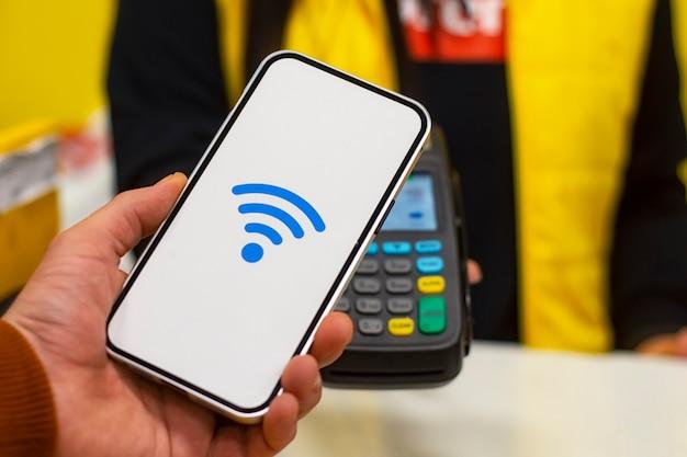 Nfc-technologie. een mannelijke koper heeft een smartphone met draadloze betaling in zijn handen