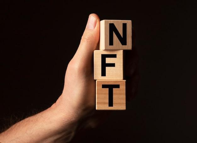 Nft-acroniem op houten dobbelstenen in mannenhand op zwarte achtergrond