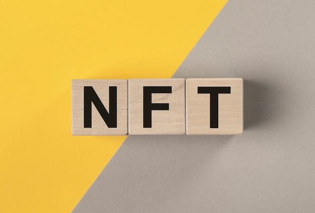 Nft-acroniem op houten dobbelstenen op gele en grijze achtergrond