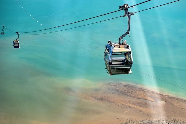 Ngong ping-kabelwagen met toeristen over haven, bergen en stadsachtergrond