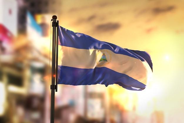 Nicaragua vlag tegen stad wazige achtergrond bij zonsopgang achtergrondverlichting