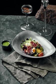Nicoise salade met tonijn, ansjovis, eieren, sperziebonen, olijven, tomaten, rode uien en slablaadjes op grijs