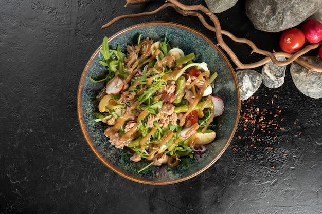 Nicoisesalade met tonijn. koud vegetarisch voorgerecht met rucola, vis, radijs, appels, kerstomaatjes en saladedressing