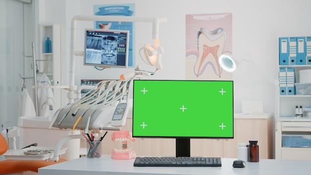 Niemand in tandartspraktijk met horizontaal groen scherm op computer