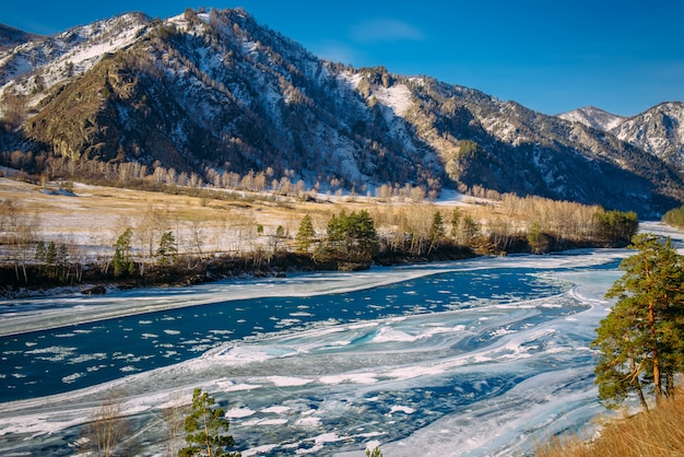 Niet-bevroren turquoise rivier in de bergen op een ijzige winterdag. ongelooflijke vallei berglandschap in zonlicht