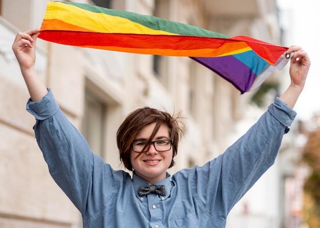 Niet-binaire persoon die de lgbt-vlag vasthoudt