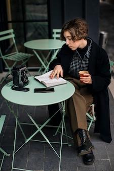 Niet-binaire persoon die notities aan een tafel leest