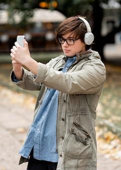Niet-binaire persoon met bril die een selfie maakt