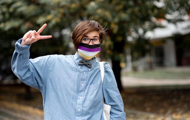 Niet-binaire persoon met bril die het vredesteken doet