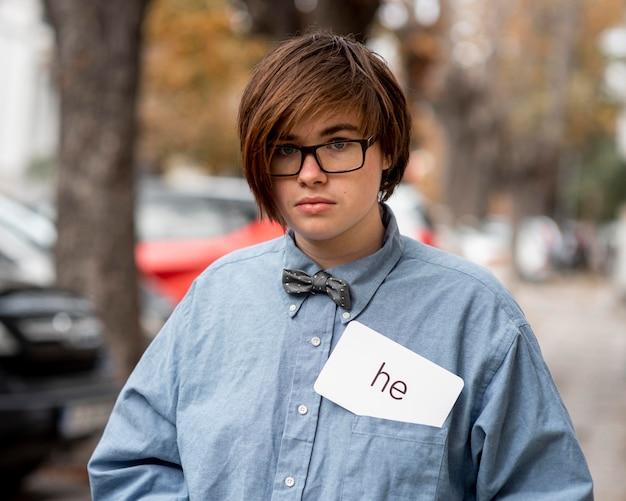 Niet-binaire persoon met een voornaamwoordkaart in een zak