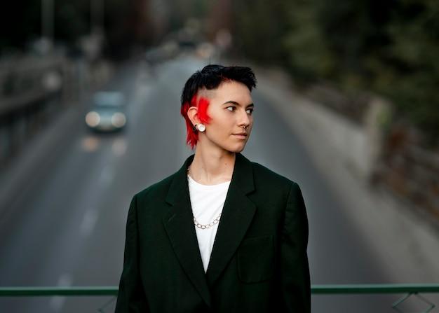 Niet-binaire persoon met modern kapsel die wegkijken poseren op een brug