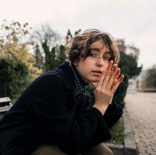 Niet-binaire persoon zittend op een bankje en hand in hand