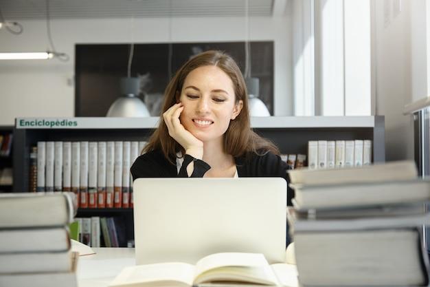 Niet-gegradueerde studentenvrouw die zich voorbereidt op examens, op laptop werkt, een draadloze internetverbinding gebruikt terwijl ze aan een bureau zit met enorme stapels boeken in de universiteitsbibliotheek, haar elleboog op tafel