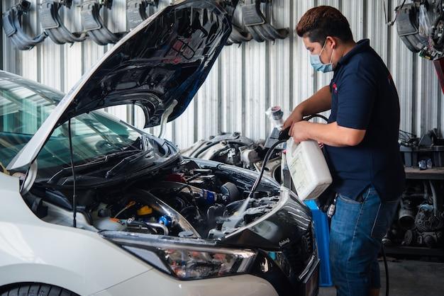 Niet-geïdentificeerde automonteur of serviceman die de motor van een auto schoonmaken na het controleren van een automotor