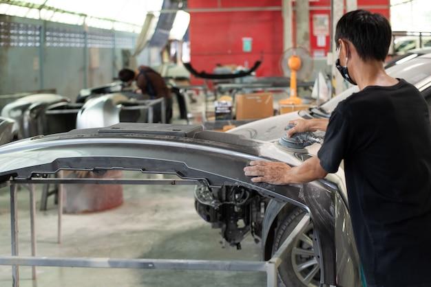 Niet-geïdentificeerde denter- of automonteur-serviceman controleert en repareert carrosserie en lichaamsdeel van vezelbumper