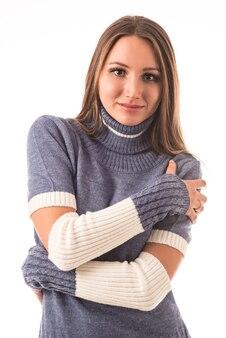 Niet-geïdentificeerde jong mooi meisje tegen de muren met een gebreide jurk en handschoenen