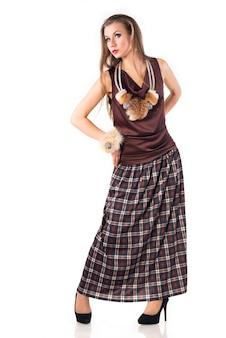 Niet-geïdentificeerde jonge vrouw in een lange rok en hoge hakken die zich voordeed op een witte achtergrond. concept van stijlvolle dameskleding. advertentie ruimte