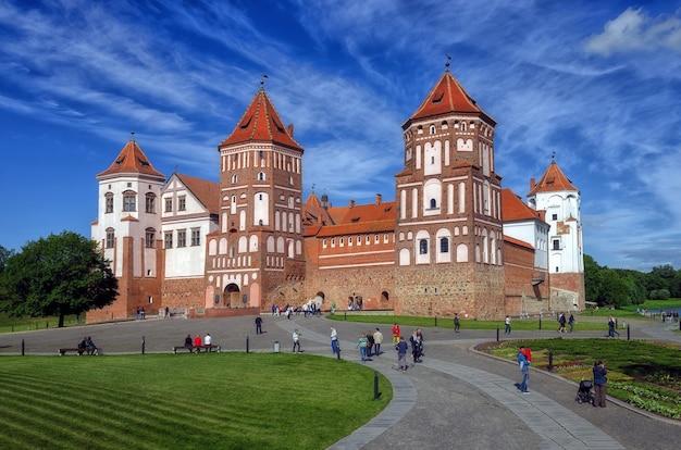 Niet-geïdentificeerde mensen lopen in de buurt van mir castle in grodno region, wit-rusland. het kasteel is een verdedigingswerk uit de xvi-xvii eeuw
