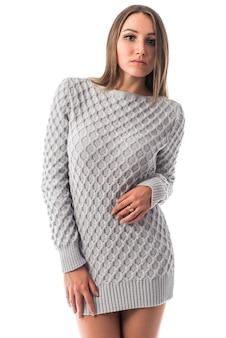 Niet-geïdentificeerde stijlvolle jonge vrouw in een grijze trui die zich voordeed op een witte muur