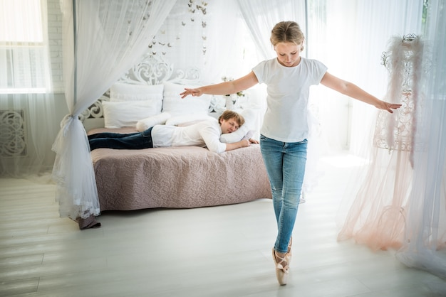 Niet-geïdentificeerde tiener ballerina twijnen op de vloer voor een vermoeide vader zittend op het bed. het concept van hyperactieve en aandachtseisende kinderen