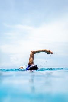 Niet-geïdentificeerde vrouw doet front crawl zwemmen in zwembad op vakantie.