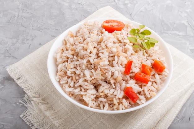 Niet gepolijste rijstepap met gestoofde groenten en orego in witte kom op een grijze concrete achtergrond