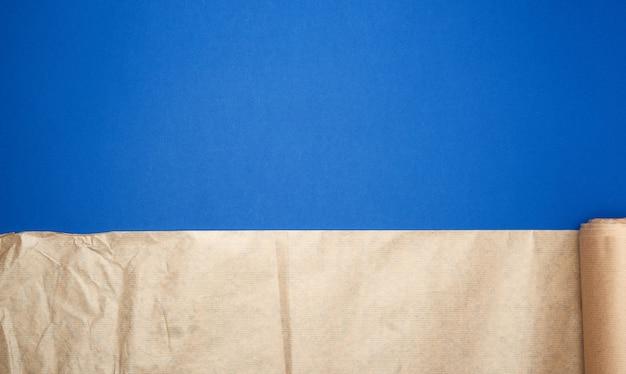 Niet getwist broodje van bruin perkamentpapier op een blauwe achtergrond
