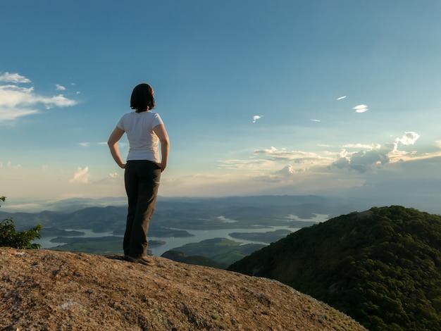 Niet-herkende mensen - meisje in het hoogste kijken van de bergtop landschap en damreservoir - backlight zonsondergang