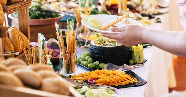 Niet-herkende persoon die eten serveert in een bord met verschillende soorten brood die worden tentoongesteld voor een buffet op tafel in een luxe restaurant. menselijke hand die voedsel in bord serveert bij het buffet van een luxehotel