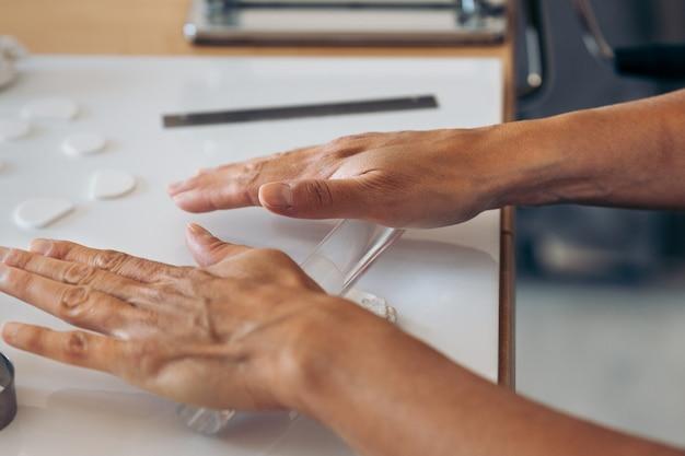 Niet-herkende vrouw die vanuit huis werkt met verschillende hulpmiddelen om prachtige handgemaakte sieraden te maken.