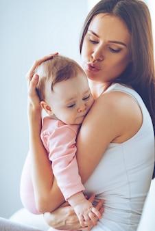Niet huilen, schat! zijaanzicht van een mooie jonge vrouw die haar babymeisje kalmeert terwijl ze haar thuis in haar armen houdt