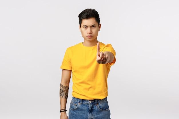 Niet meer, stop ermee. ernstig ogende vastberaden jonge knappe aziatische man met tatoeages, uitgestrekte arm en schuddende wijsvinger in taboe, verbieden of verbieden gebaar, fronsend, witte muur