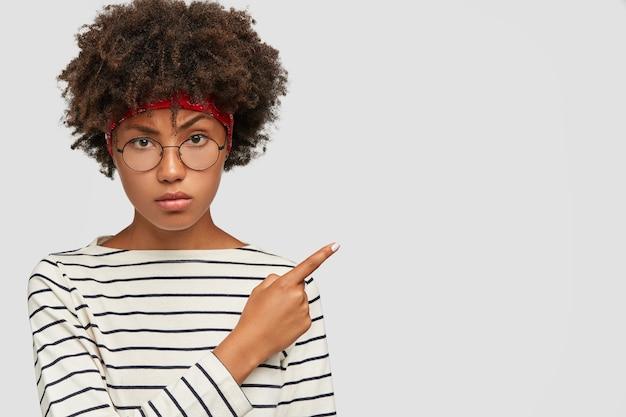 Niet onder de indruk neerslachtig zwart meisje trekt wenkbrauw op, voelt zich ongelukkig