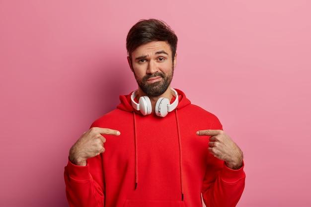 Niet onder de indruk ongeschoren blanke man wijst naar zichzelf, vraagt naar wie ik ben, heeft een rustige gezichtsuitdrukking, draagt een rood sweatshirt, luistert naar audio via headset, toont nieuw gekochte outfit, poseert over roze muur