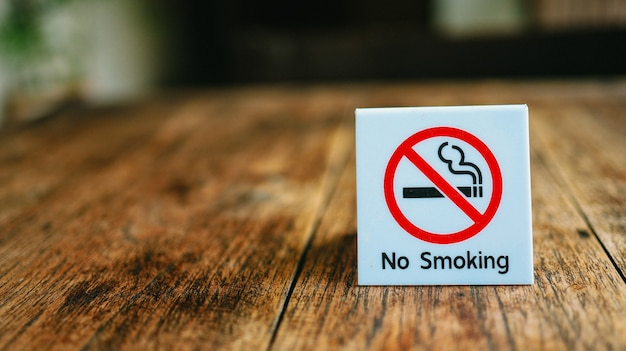 Niet roken teken no smoking label in the public geen teken van roken op houten tafel in het hotel