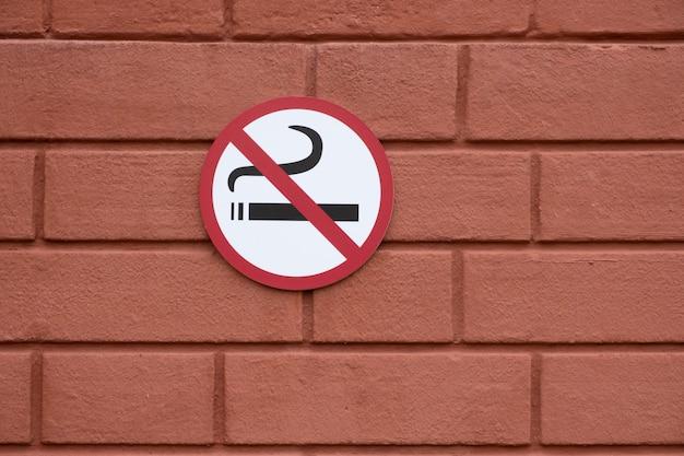 Niet roken teken op een rode bakstenen muur. kopieer ruimte.