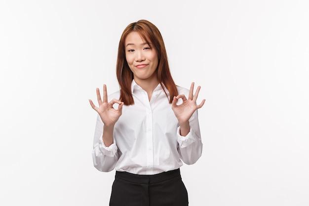 Niet slecht. aziatische kieskeurige vrouwelijke baas geeft haar feedback over het product, goed maar niet de beste, toont een goed gebaar en grijnst goedkeurend, knikt tevreden, gaat akkoord of vindt iets goed, normaal