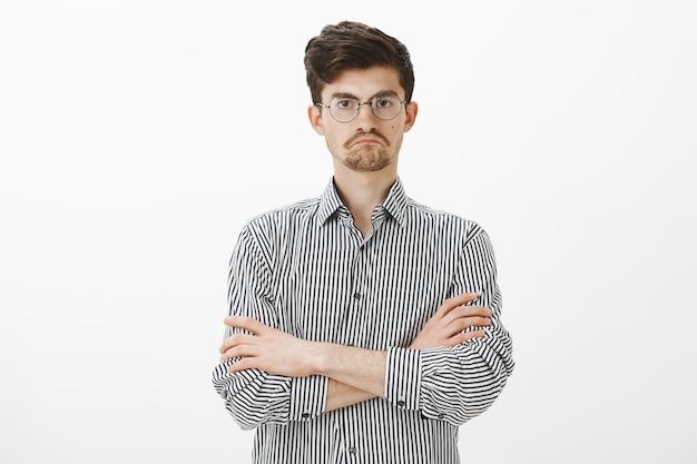 Niet slecht eigenlijk. portret van respectvolle tevreden strikte europese werknemer, hand in hand op de borst gekruist en een tevreden steurgezicht makend terwijl hij iets bevredigend over grijze muur ziet