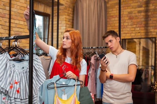 Niet weer. uitgeput jongeman bedachtzaam met een moderne smartphone terwijl zijn mooie vriendin kleren kiezen