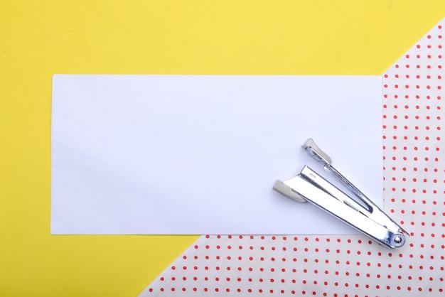 Nietmachine en leeg wit papier met een gekleurde achtergrond. leeg witboek voor exemplaarruimte