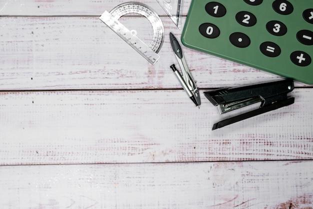Nietmachine, kompas, linialen en rekenmachine op planken