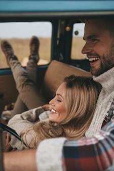 Niets anders dan liefde. aantrekkelijke jonge vrouw rusten en glimlachen terwijl haar vriendje rijden retro-stijl minibusje