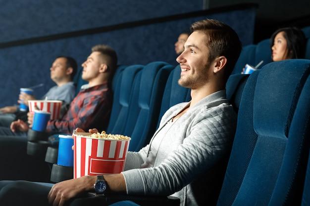 Niets beter dan een goede film. vrolijke casual man tijd doorbrengen kijken naar film met snacks in de plaatselijke bioscoop