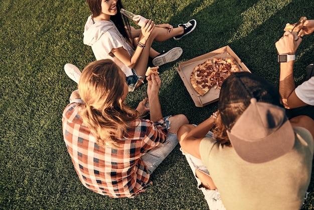 Niets dan goede vrienden. bovenaanzicht van jonge lachende mensen in vrijetijdskleding die genieten van pizza en bier terwijl ze buiten op het gras zitten