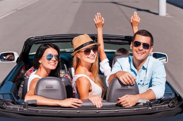 Niets dan vrienden en roadtrip. bovenaanzicht van jonge gelukkige mensen die genieten van een roadtrip in hun witte cabrio en glimlachen