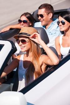 Niets dan vrienden en roadtrip. bovenaanzicht van jonge gelukkige mensen die genieten van een roadtrip in hun witte cabrio