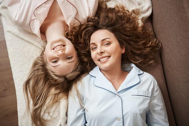 Niets is sterker dan die vriendschap. twee mooie europese vrouwen liggend op de bank in comfortabele nachtkleding, vrije tijd samen doorbrengen, breed glimlachend, meisjesachtige gesprekken