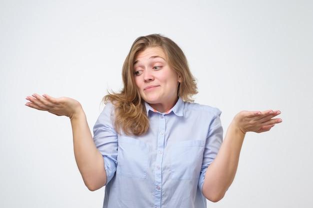Nietsvermoedende vrouw haalt onzeker schouders op van hulpeloosheid